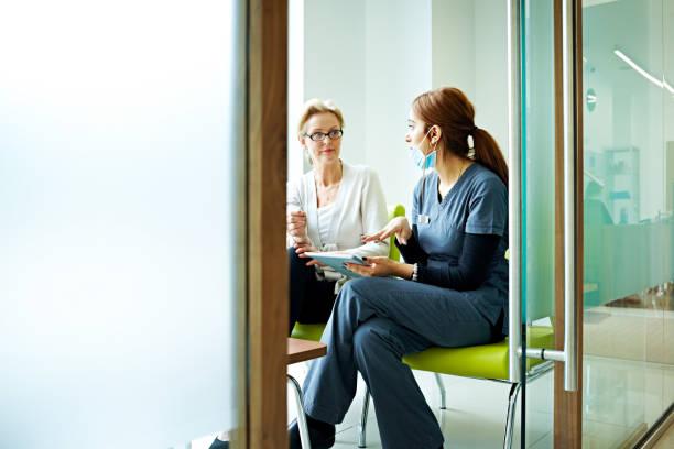 female dentist discussing report with patient - two dentists talking bildbanksfoton och bilder