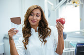 istock Female dentist holding  apple and a chocolate 1130138675