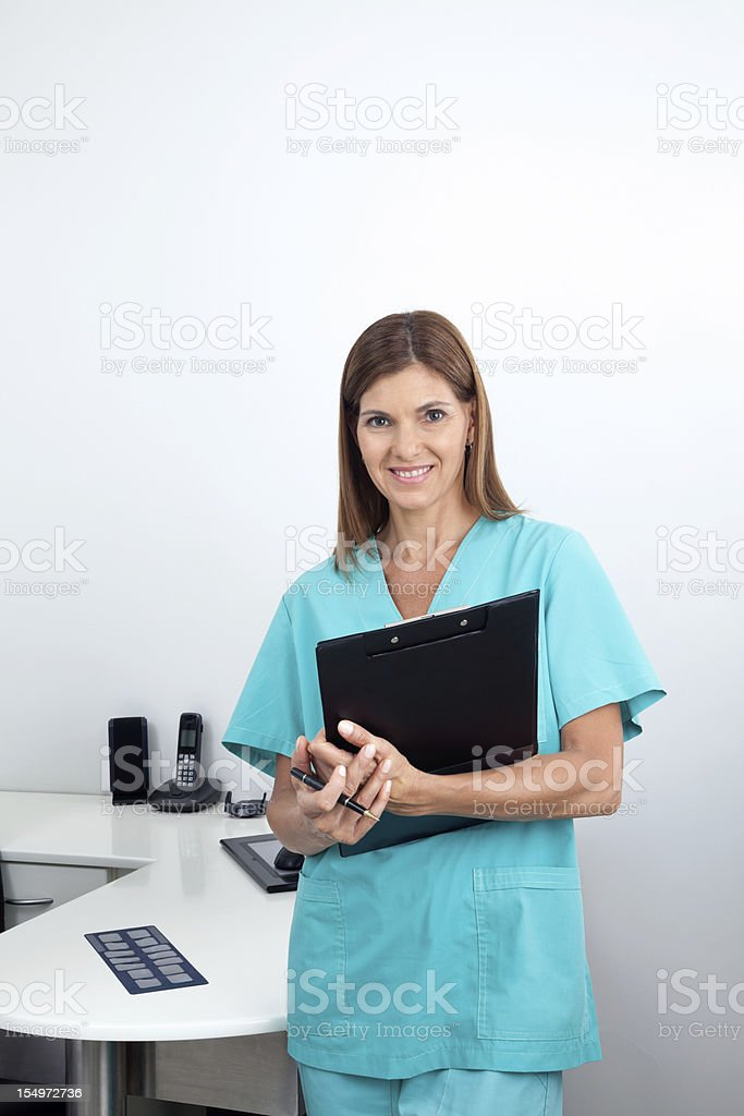 Female Dentist Holding Clipboard In Clinic royalty-free stock photo