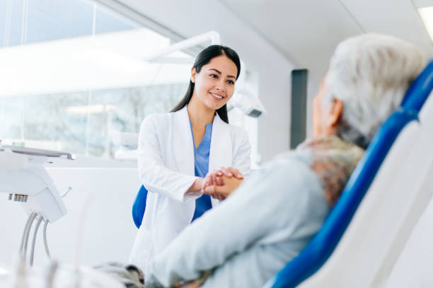 Female dentist holding hand of senior patient stock photo