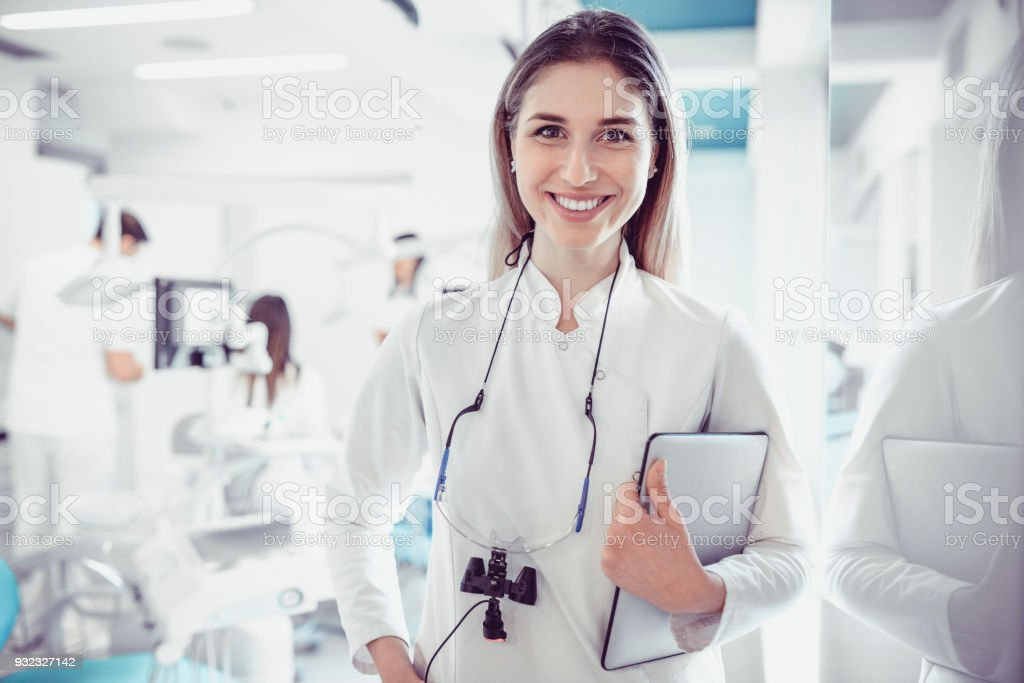 Female Dentist in Dental Clinic with Working Medical Team Behind Her stock photo