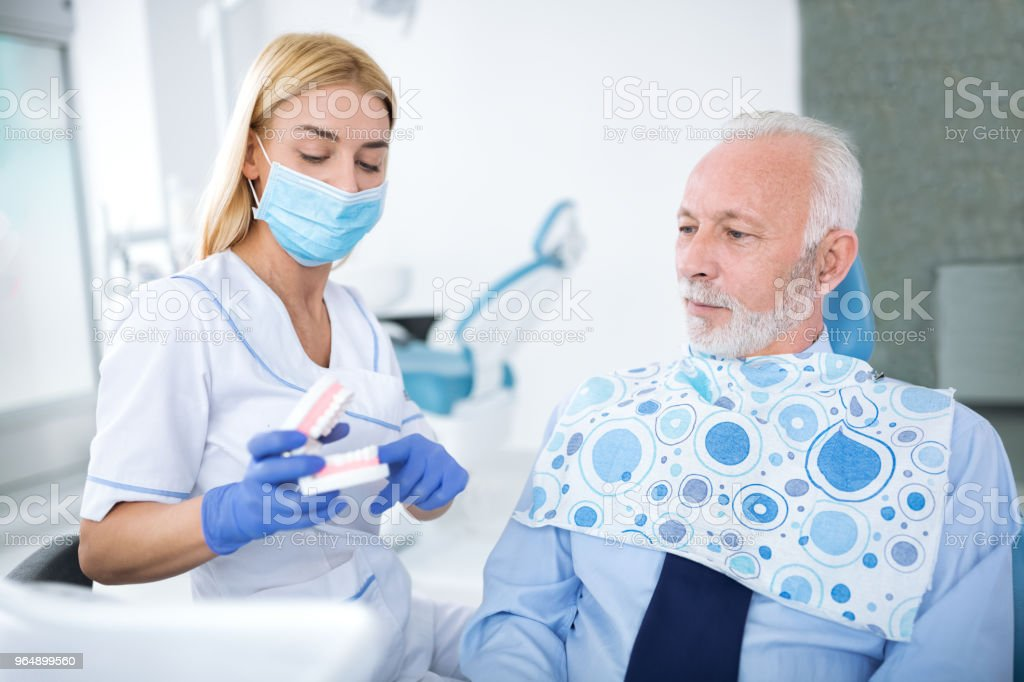 Female dentist shows patient appearance of tooth royalty-free stock photo