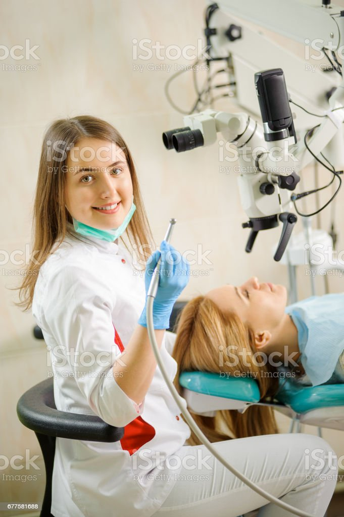 Female dentist treating caries using microscope at the dentist office royalty-free stock photo