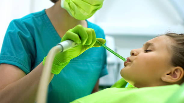 Female dentist using saliva ejector, teenage girl sitting in chair frowning Female dentist using saliva ejector, teenage girl sitting in chair frowning suction tube stock pictures, royalty-free photos & images