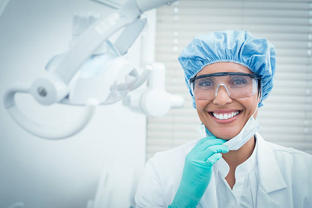 Female dentist wearing surgical cap and safety glasses stock photo