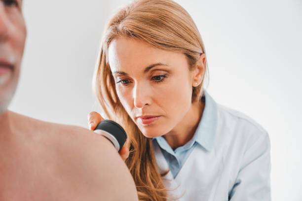 Female dermatologist examines skin moles or acne of senior patient with dermatoscope Female dermatologist examines skin moles or acne of senior patient with dermatoscope dermatologist stock pictures, royalty-free photos & images