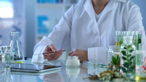 Female dermatologist testing new hand cream, applying on skin with metal stick stock photo