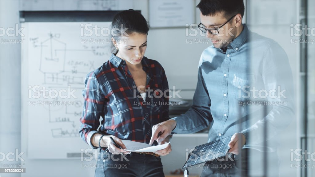 Female Design Engineer Works on Documents in a Conference Room, Last Minute Check-up, Uses Her Smartphone. In the Background Whiteboard with Schemes on it, Various Blueprints Hanging on the Walls. stock photo