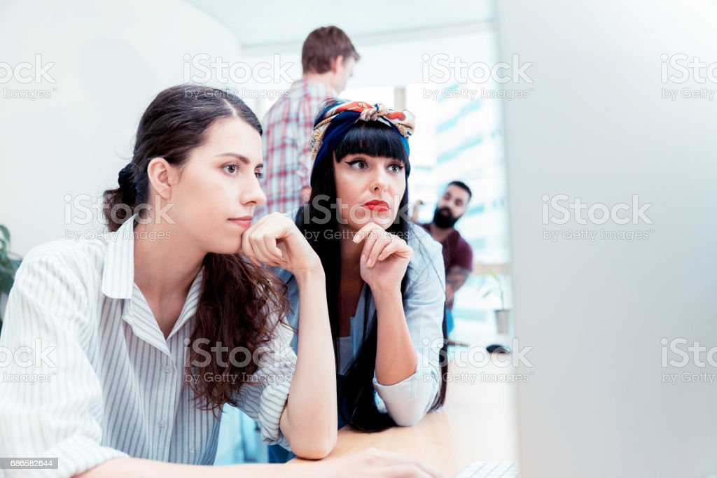 Female design professionals working together on a computer at their office royalty-free stock photo