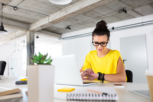 Female Designer Checking Time In Office Stock Photo - Download Image Now