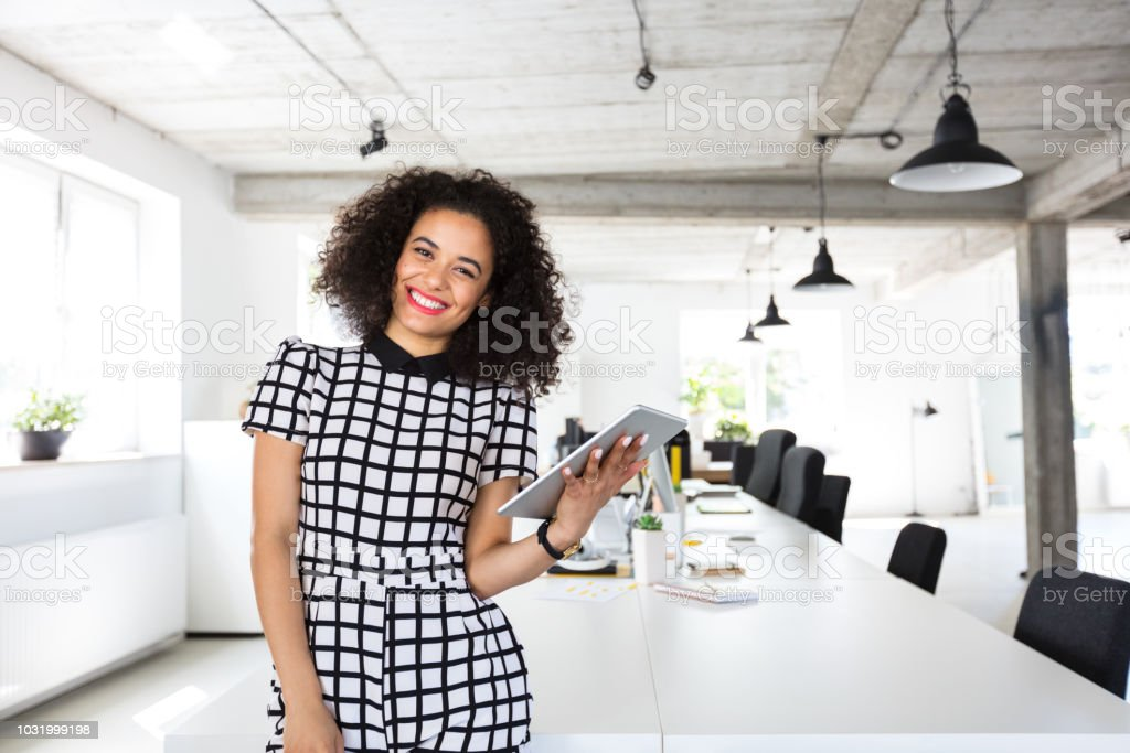 Female designer in modern work place Portrait of beautiful young woman with curly hair standing at a table with digital tablet in hand. Female designer in modern work place. 20-24 Years Stock Photo