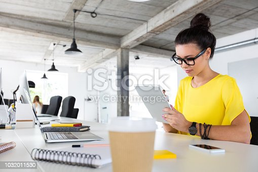 Young woman sitting at her desk and working on digital tablet. Female designer using tablet pc in office.