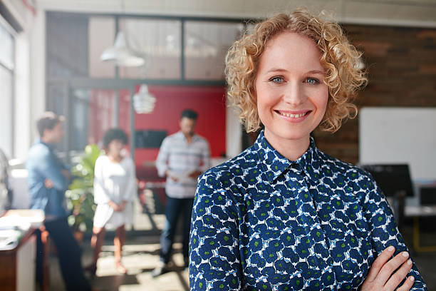 Female designer with colleagues in the background at office Portrait of a smiling young female designer standing in her office with some colleagues in the background. incidental people stock pictures, royalty-free photos & images