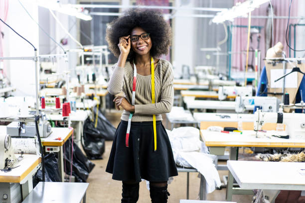 Female designer with tape measure in factory Female designer with tape measure working in fashion studio. fashion designer stock pictures, royalty-free photos & images