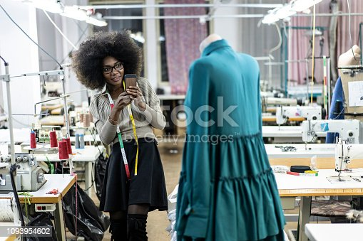 Female designer with tape measure working in fashion studio.