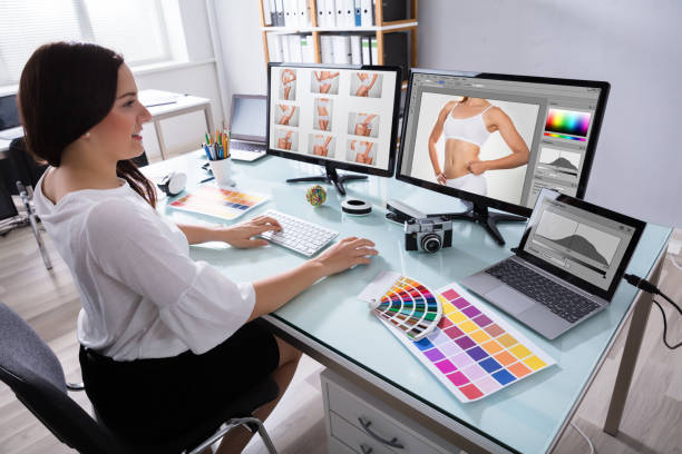 female designer working with photographs on multiple computer - retouched image stock photos and pictures