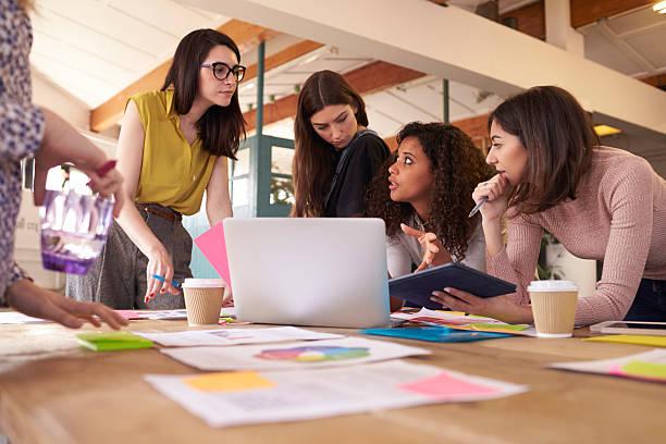 Female Designers Having Brainstorming Meeting In Office stock photo