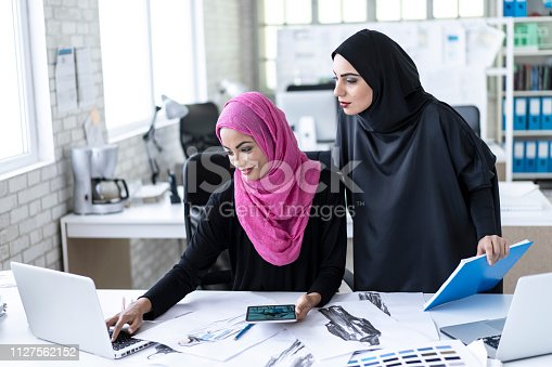 Arab fashion designers choosing colors and models in studio, using laptop and tablet.