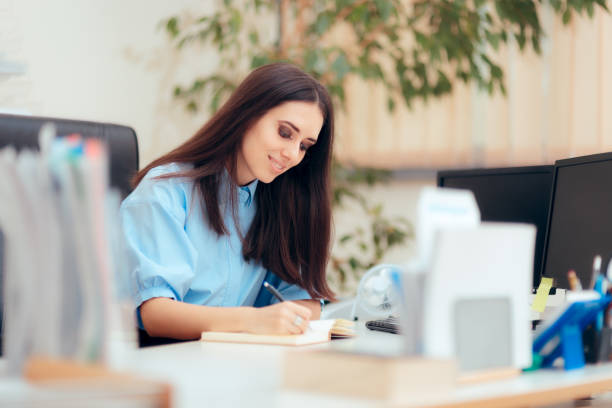 Female Desk Job Office Employee Working To Complete Tasks Busy woman having a desk job in corporate building administrator stock pictures, royalty-free photos & images