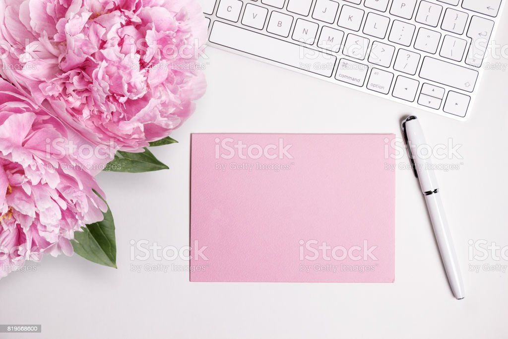 Female desktop with white keyboard and pink peonies, top view mock up stock photo