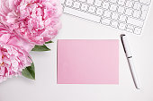 Female desktop with white keyboard and pink peonies, top view mock up