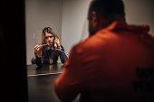 Female detective interrogating a prisoner in prison visiting room.