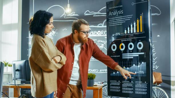 Weibliche Entwickler und männliche Statistiker Verwendung interaktive Whiteboard Präsentation Touchscreen, Blick auf Diagramme, Grafiken und Statistiken Wachstum. Sie arbeiten in der stilvollen Kreativbüro. – Foto