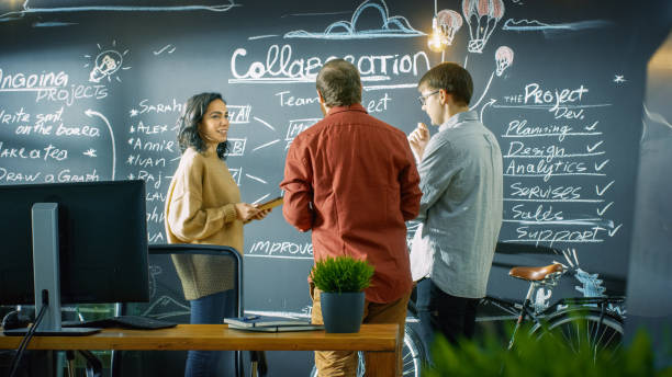 développeur féminin avec tablette ordinateur pourparlers avec programmeur et chef de projet, ils utilisent blackboard mur comme un planificateur. ils travaillent dans le bureau de style créatif. - chef de projet photos et images de collection