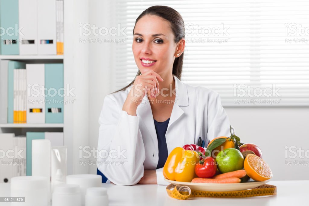 Female dietician showing vegetables and fruit – Foto