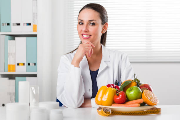 Female dietician showing vegetables and fruit stock photo