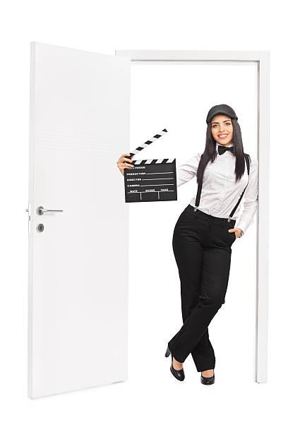 weibliche director hält ein clapper angelehnt an tür - klappe hut stock-fotos und bilder