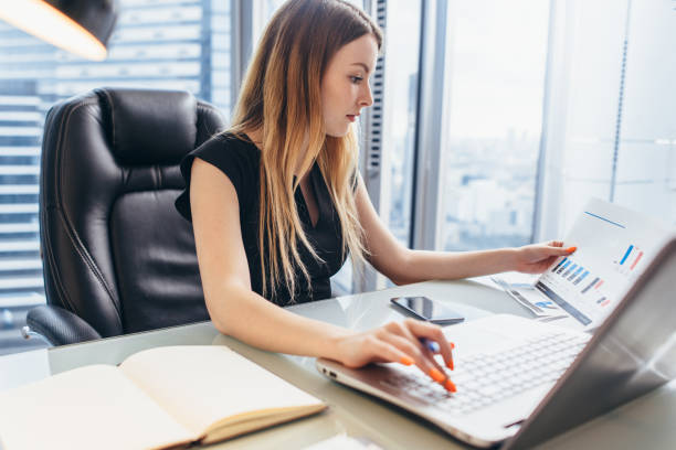 Female director working in office sitting at desk analyzing business statistics holding diagrams and charts using laptop stock photo