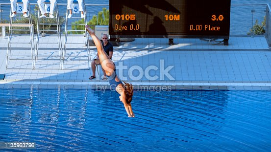 Diving judge looking at female diver diving into swimming pool.