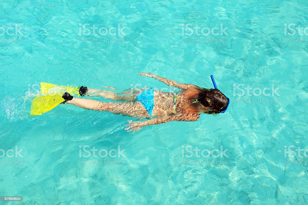 Female diver with yellow flippers snorkeling in blue sea. royalty-free stock photo