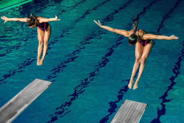 Female divers Two female divers diving into the pool. Tandem diving symmetry stock pictures, royalty-free photos & images