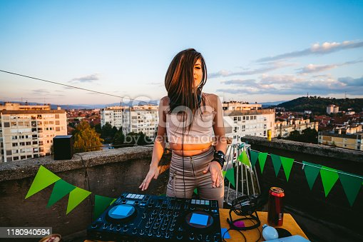 Young Caucasian beautiful female dj dancing and playing music at rooftop party.