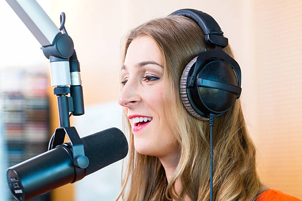 Female dj wearing headphone in front of microphone Female presenter or host in radio station hosting show for radio live in Studio radio dj stock pictures, royalty-free photos & images