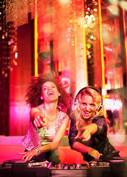 Female DJs in nightclub stock photo
