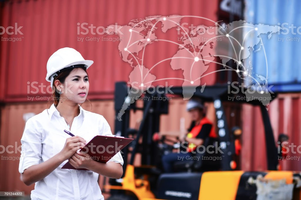 Female dock worker control loading Containers box to truck for Logistic Import Export Background stock photo