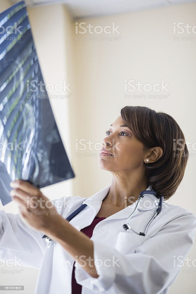 Female Doctor Analyzing X-ray Report In Clinic royalty-free stock photo