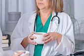 female doctor and a young nurse keep cups of coffee in hands and gossip with each other during coffee break in the staff room