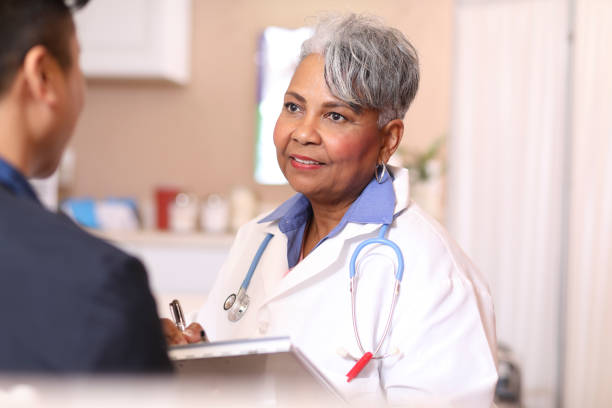 Female doctor and adult patient in office, clinic. Female, African descent doctor or mental health professional gives medical advice or provides therapy to adult patient in office or clinic setting.  Medical exam, consultation, therapist. covid-19 stock pictures, royalty-free photos & images