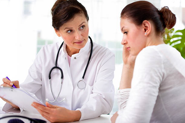 Female doctor and female patient looking over clipboard stock photo
