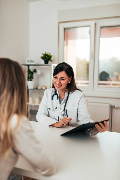 Female doctor and female patient talking about test results. stock photo