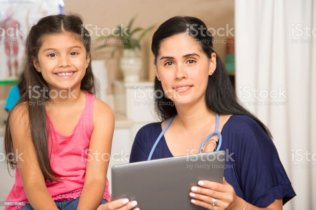 Female doctor and latin descent girl patient in pediatrician's office or clinic. stock photo