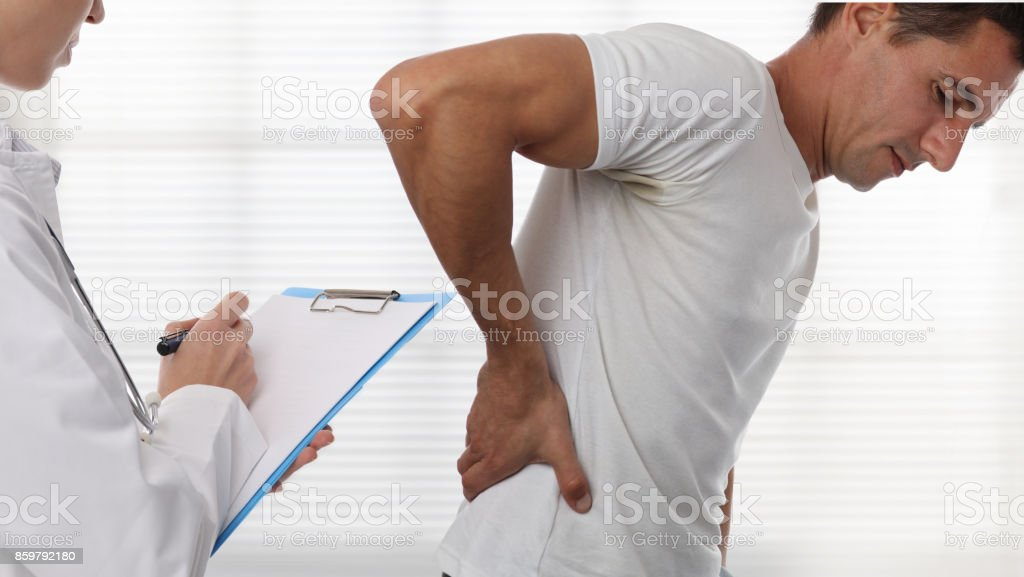 Female Doctor and male patient suffering from back pain during medical exam. stock photo