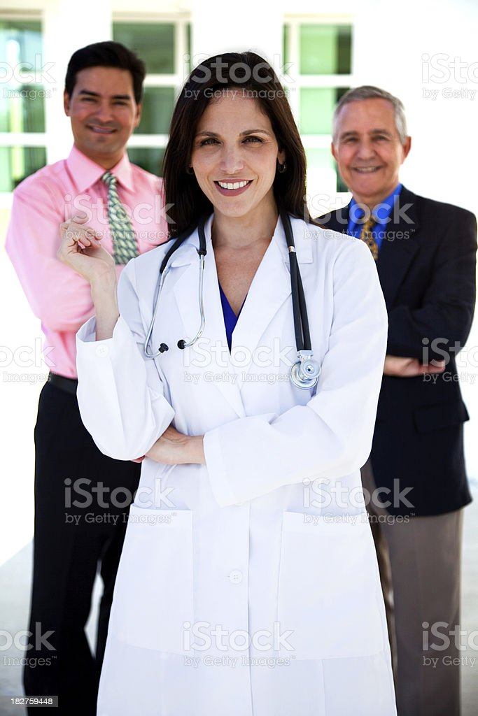 Female doctor and two businessmen in background royalty-free stock photo