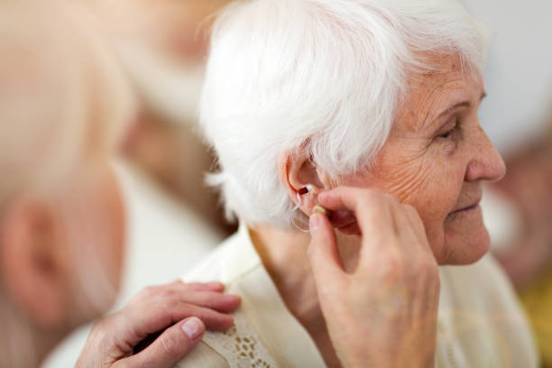 female doctor applying hearing aid to senior woman's ear - hearing loss stock pictures, royalty-free photos & images