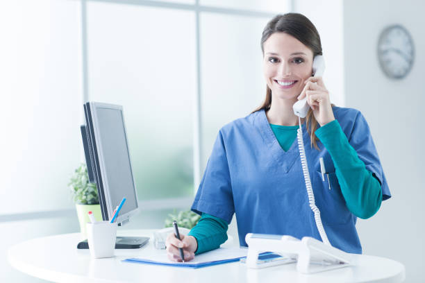 female doctor at the reception desk - nurse on phone stock photos and pictures