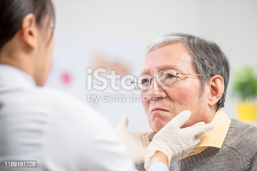 1049772134istockphoto Female doctor check throat 1159191728